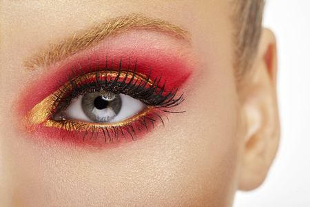 stage make up: Make up beauty close up. Eye with red and gold make up in close up photo. Fantasy on stage make up