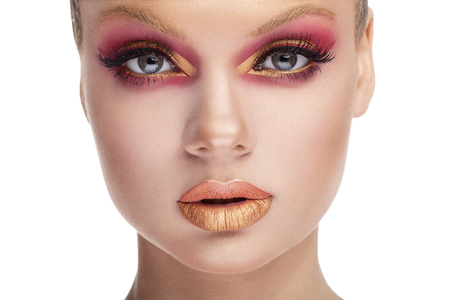 fashion art: Woman looking at camera with red and gold make up. Fashion art beauty make up