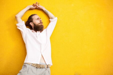 outside shooting: Good looking hipster posing on yellow wall in outside shooting