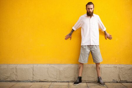 outside shooting: Hipster with long beard on yellow wall in outside fashion shooting