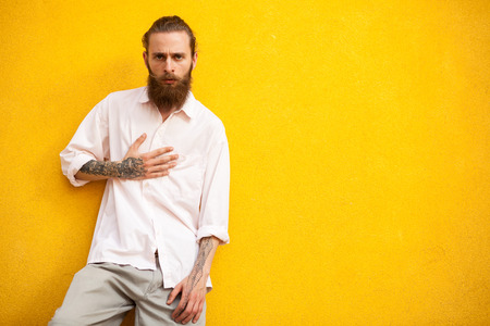 outside shooting: Cool looking bearded men lying on yellow wall in outside fashion shooting
