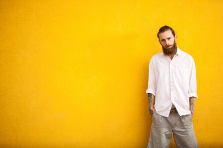 outside shooting: Long bearded hipster on yellow wall in outside fashion shooting Stock Photo