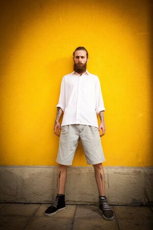 outside shooting: Bearded hipster looking in camera on yellow wall in outside fashion shooting
