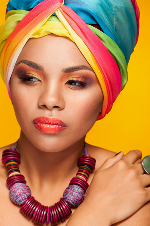 black makeup: Beautiful ethnic afrom american young model wearing a turban on yellow background in studio photo