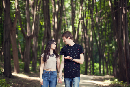 happines: Couple walking and smiling each other in the forest. Happines and activity in two