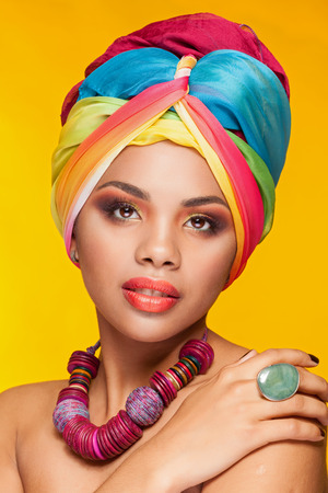 vibrant colors: Gorgeous afro american ethnic girl with turban on her head on yellow background in studio photo. Beauty and culture