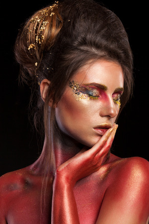 Creative make up with glitter, gold and red colors on black background in studio photo. On stage and art beauty make up Stock Photo