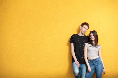 outside shooting: Cool couple looking in the camera on yellow wall in outside shooting