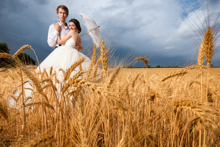 wedding photography: Bride and groom in wheat field with dramatic sky on the background. Wedding photography. Happy just maried couple