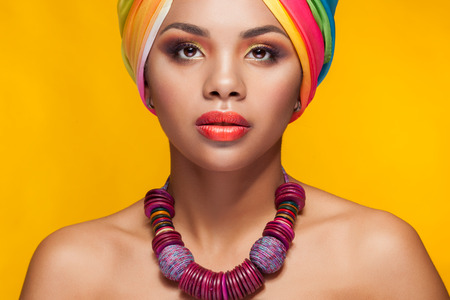 Afro american girl in national turban over yellow background in studio photo. Beauty and fashion portrait