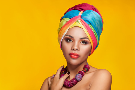 Beautiful afro american girl wearing a national turban over yellow background in studio photo