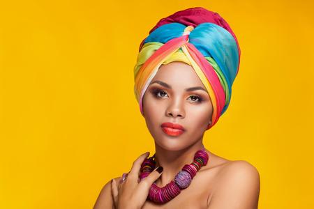 Bella ragazza afro americana che indossa un turbante nazionale su sfondo giallo in studio fotografico