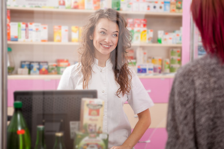 Smiling pharmacist to her client in the drugstore. Healthcare business Stock Photo