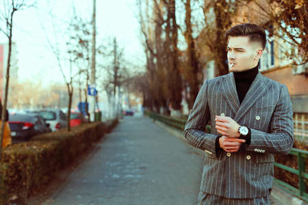 cool guy: Cool men in fashion suit smoking a cigarette outside in the street. Fashion toning image. Beautiful looking guy Stock Photo