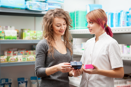 Doctor and client in warehouse looking at two boxes of pills