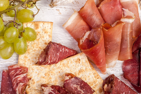 Different type of delicous ham, grape and crackers on white wooden background. Healthy food