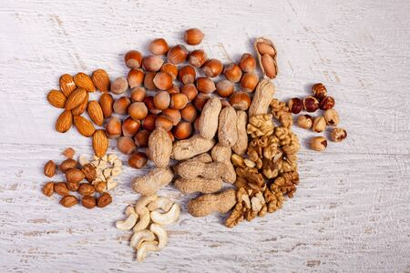 Different type of nuts of white wooden background. Healthy food