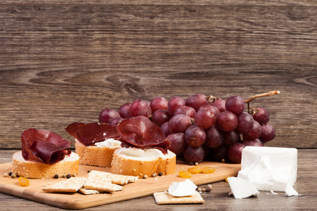 Ham, white cheese and grape on wooden background. Healthy food