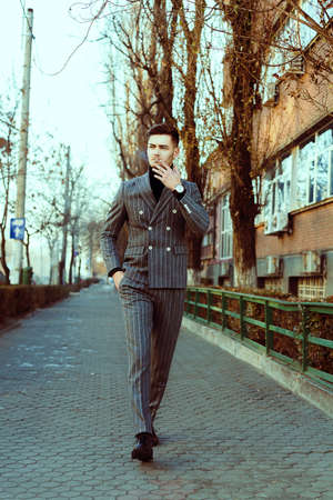 cool guy: Cool looking guy in fashion suit outdoor smooking. Fashion image. Outdoor winter shooting
