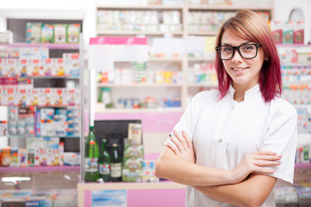 Young pharmacist in glasses inside a pharmacy looking at camera and smiling Stock Photo