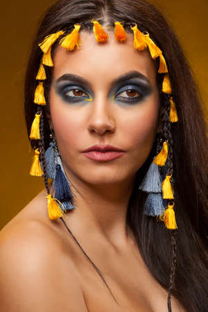 Beautiful woman with creative make up on yellow background in studio photo. Creative and beauty image. Glamour portrait