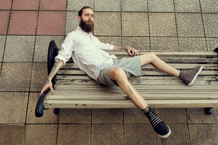 Cool looking guy with tatoos and long beard sitting on chair posing at camera and posing in fashion style. Nonconformism and hipster