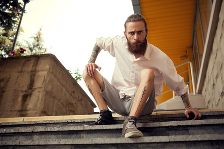 cool guy: Cool looking guy sitting in street on stairs looking away from the camera Stock Photo