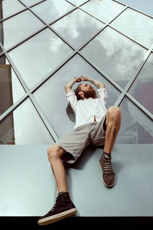 Cool looking guy with tatoos and long beard in front of office building posing at the camera. Lifestyle Stock Photo