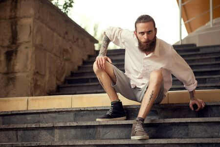 cool guy: Beardead tattooed cool looking guy sitting in street on stairs looking away from the camera