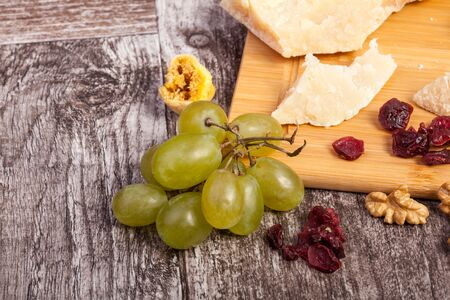 Different type of cheese, honey and grape on wooden background in studio photo