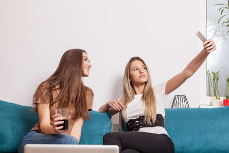 Two female friends taking a selfie on the sofa Stock Photo