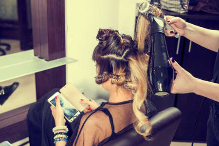 comb: Woman looking at smartphone while getting a hairstyle. Professional service. Beauty and treatment Stock Photo
