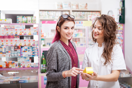 advise: Pharmacist and her client in front of the desk. Healthcare business