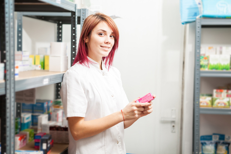 Pharmacist woman in the storage facility next to the shelfs. Healthcare business