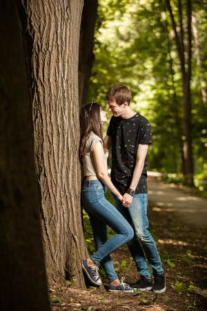 Young couple taking a walk in the forest. Lifestyle and relationship. Young inlove boyfriend and girlfriend
