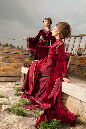 Two women in vintage clothes on a boat. Luxury and glamour