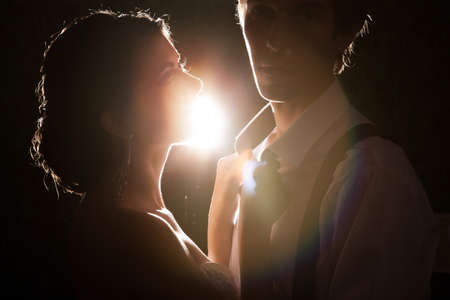 Beautiful bride and groom together backlit in vintage interior. Happiness and marriage Stock Photo