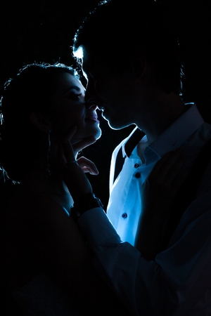 Gorgeous bride and groom backlit with blue light. Happiness and marriage