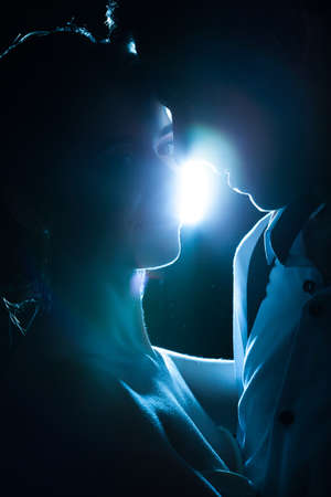 Beautiful bride and groom backlit with blue light. Happiness and marriage