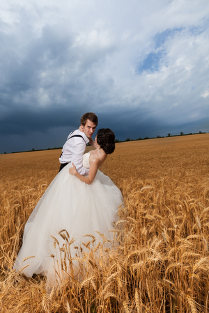Beautiful bride and groom in wheat field. Happiness and marriage Stock Photo