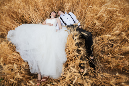 Bride and groom lying in wheat field. Happiness and marriage Stock Photo