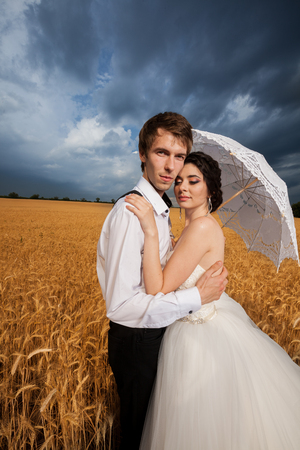 Inlove bride and groom in wheat field. Happiness and marriage
