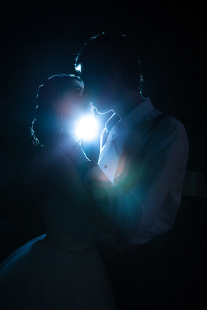 Beautiful inlove bride and groom backlit with blue light. Happiness and marriage