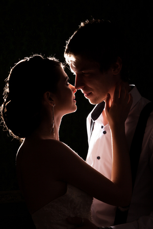 Gorgeous bride and groom together backlit in vintage interior. Happiness and marriage Stock Photo
