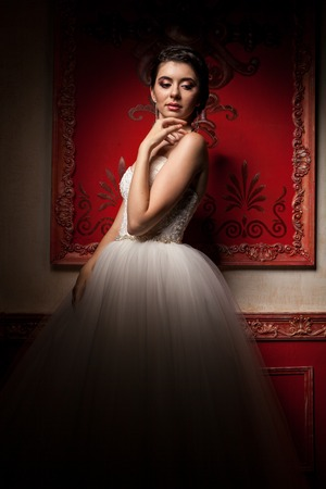 Gorgeous bride in red vintage interior. Happiness and marriage Stock Photo