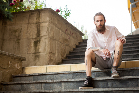 Tattoed and bearded guy posing outdoor in the city Stock Photo