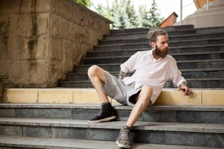 Fashion tattoed and bearded guy posing outdoor in the city