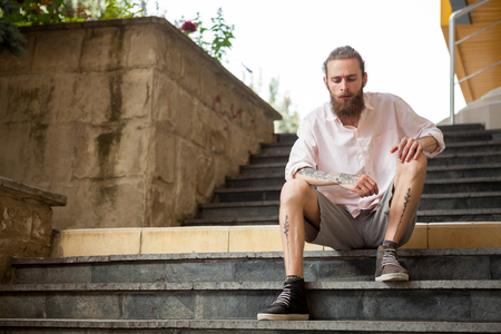 Cool tattoed and bearded guy posing outdoor in the city Stock Photo