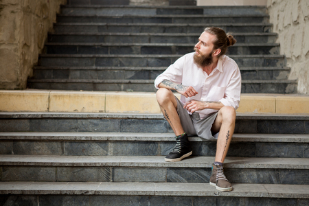 Tattoed guy posing outdoor in the city Stock Photo