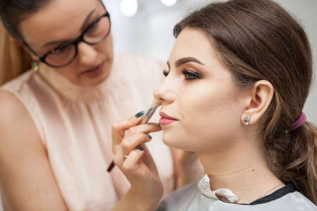 Brunette model at a makeup masterclass. Applying make up to a young beautiful model